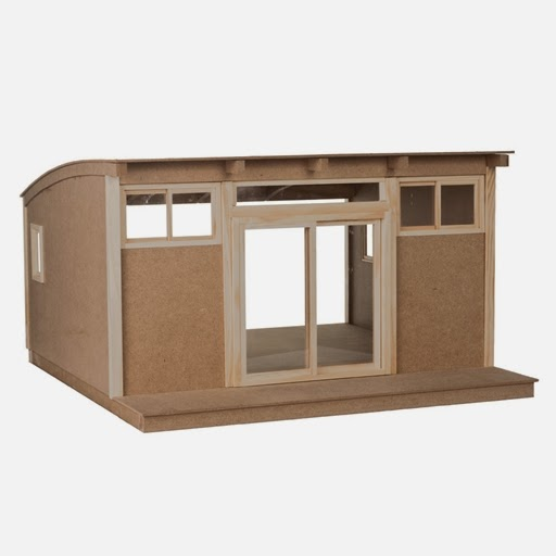 Photo of a modern dolls' house miniature shed kit with curved roof and sliding doors at the front.