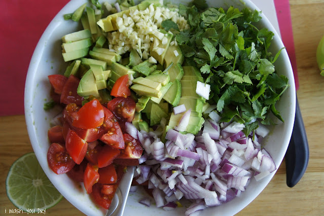 A display of chopped veggies needed to make fresh guacamole: guacamole, cilantro, onions, tomatoes, garlic