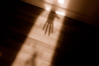 Lit outline of a person, with an ominous dark hands inside of it.