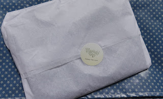 The bib wrapped up in white tissue paper sealed with a sticker with the Messy Me logo on, on top of the folded up messy mat.