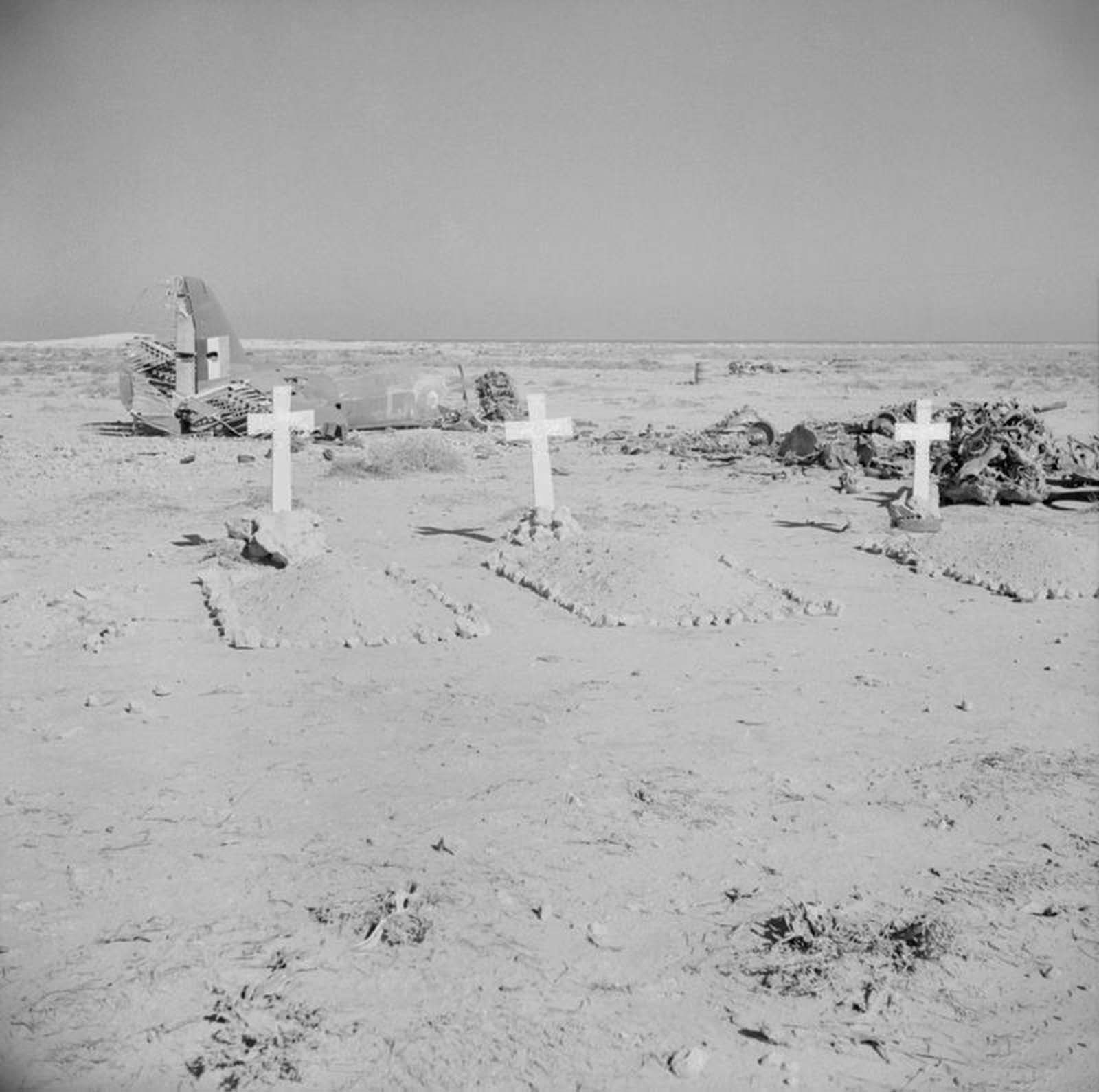 The graves of three aircrew of No. 39 Squadron RAF, buried by the Germans, lie in front of the wreckage of their Martin Maryland Mark II south-west of Gazala.