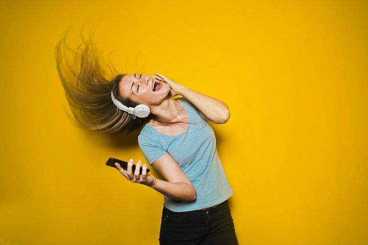 seorang wanita sedang asik mendengarkan musik dari headphone