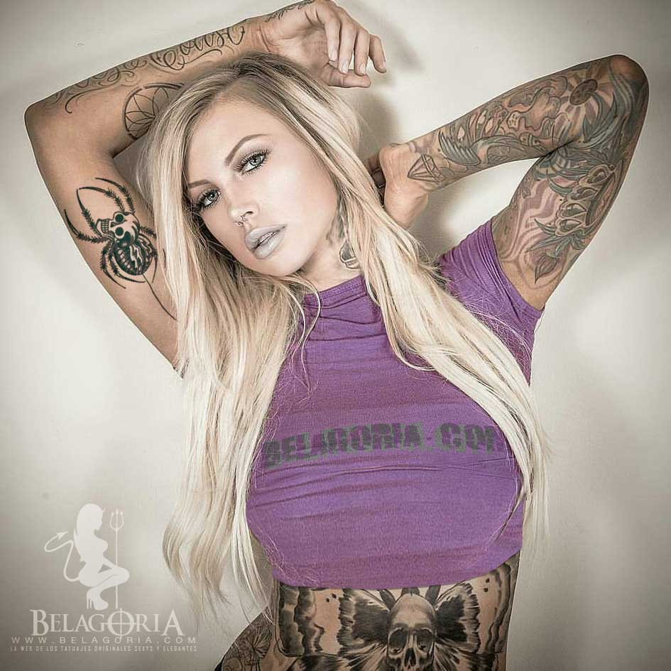 Foto de una modelo rubia con tatuaje de tarantula en el interior del brazo