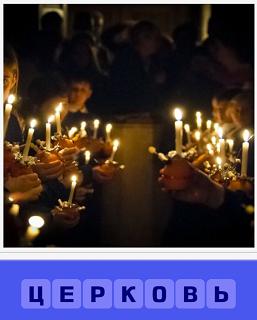 помещение церкви и внутри стоят горящие свечи у людей в руках
