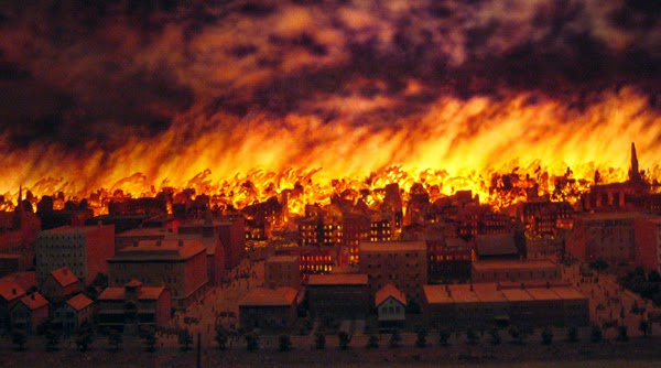 horror movie city on fire as people die running from zombie hordes.