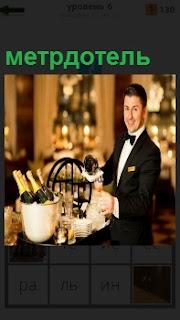 Около стола, где стоят бутылки с шампанским открывает их метрдотель в костюме