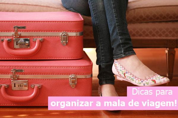 Dicas para organizar a mala de viagem. Malas de viagem rosa empilhadas uma em cima da outra e mulher sentada com as pernas cruzadas.