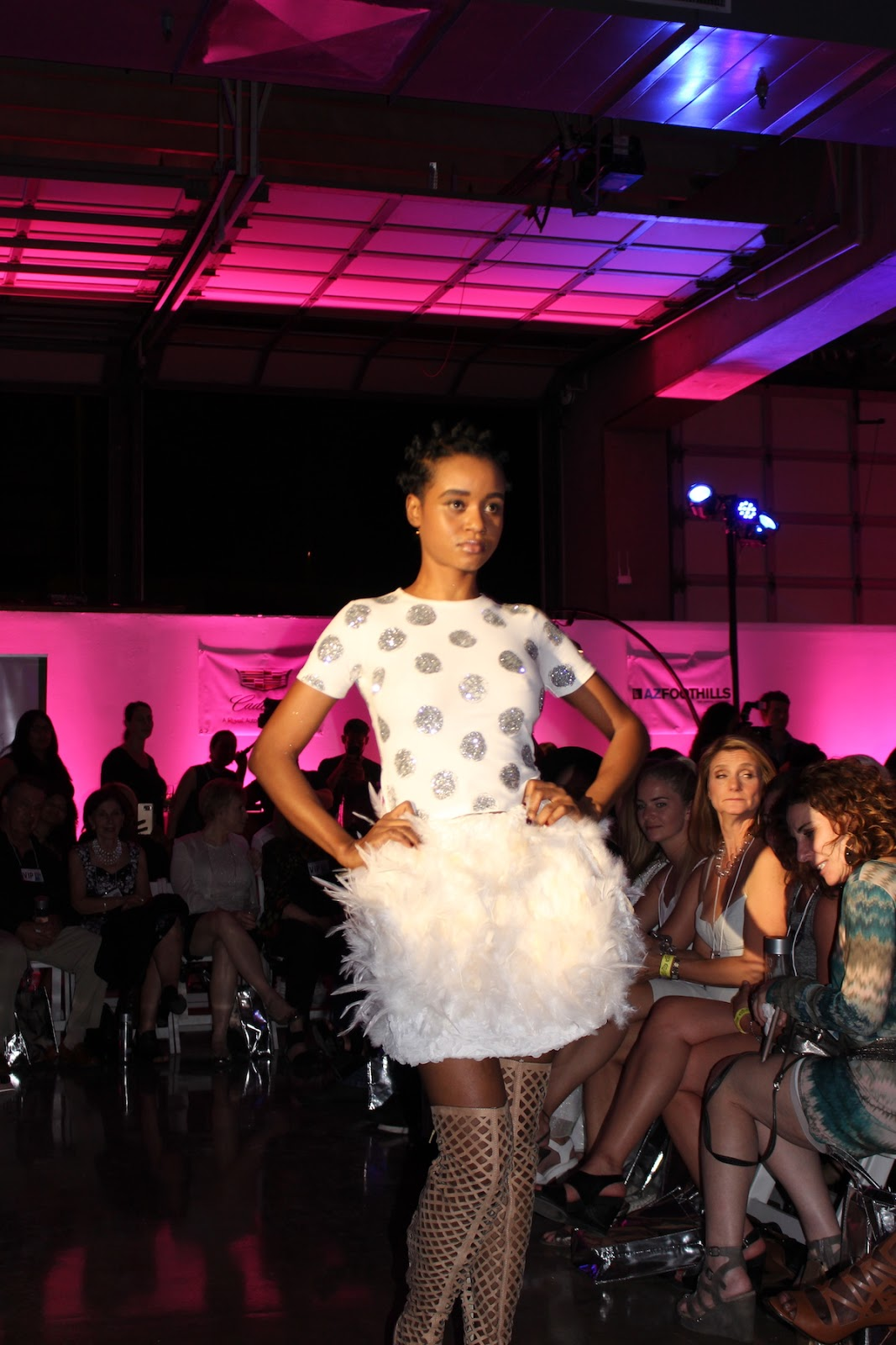 My favorite model is wearing a white and silver polka dot top, along with a poofy skirt. She is rocking it down the runway with a lot of personality.