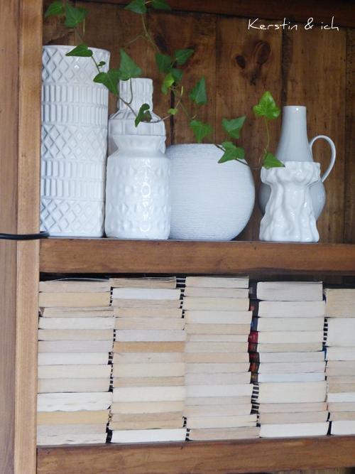 Bücherregal Büchersortierung liegend und weiße Vasensammlung