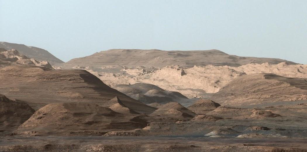 Khung cảnh hùng vĩ này là vùng cao hơn của Núi Sharp được chụp vào ngày 9 tháng 9 năm 2015 bởi tàu Curiosity của NASA. Ở tiền cảnh, cách 3 km so với vị trí của tàu, là một dãy núi đầy ắp hematite, hay oxid sắt. Ra xa hơn một chút, là khu vực giàu có khoáng chất sét. Những ngọn đồi với phần chóp tròn ở xa hơn, chứa nhiều khoáng chất sulfat. Sự thay đổi khoáng vật đa dạng ở Núi Sharp cho thấy sự thay đổi môi trường rõ rệt trong Sao Hỏa từ những ngày đầu tiên khi hành tinh vừa được tạo thành, các nhà khoa học cho rằng chúng có liên quan đến sự tiếp xúc ở các với mức độ khác nhau với nước ở từng khu vực khác nhau vào hàng tỷ năm trước. Ở xa nhất, là những vách đá có thể được hình thành khi Sao Hỏa đã khô cạn, hiện đang bị xói mòn nghiêm trọng bởi gió thổi mạnh. Màu sắc trong ảnh này đã được chỉnh sửa sao cho giống với màu sắc của từng loại khoáng sản tương ứng khi nhìn thấy ở Trái Đất, giúp các nhà địa chất xác định được từng loại đá dễ dàng. Việc cân bằng trắng hình ảnh khiến bầu trời Sao Hỏa thường có màu xanh hoặc đôi khi là màu xám, màu đen. Hình ảnh: JPL-Caltech/MSSS/NASA.