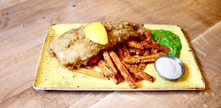 a white rectangular plate containing a long light brown battered Cod fillet with a circular wedge of yellow Lemon on top of it, a stack of long rectangular chunky Sweet Potato Fries and a pile of bright vivid green Mushy Peas next to it, with a small oval white bowl next to it containing a white Tartare Sauce on a light brown wooden rectangular table on a bright background