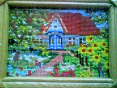 domek w ogrodzie pełnym kwiatów wyszyty haftem krzyzykowym
