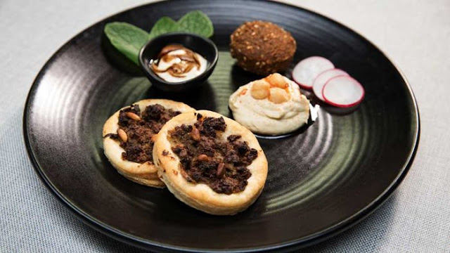 lahma bi agin, falafel, hummus, radish and tahini pomegranate molasses dip in a serving dish
