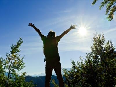 mulher-de-bracos-abertos-ao-sol-e-natureza-ao-fundo