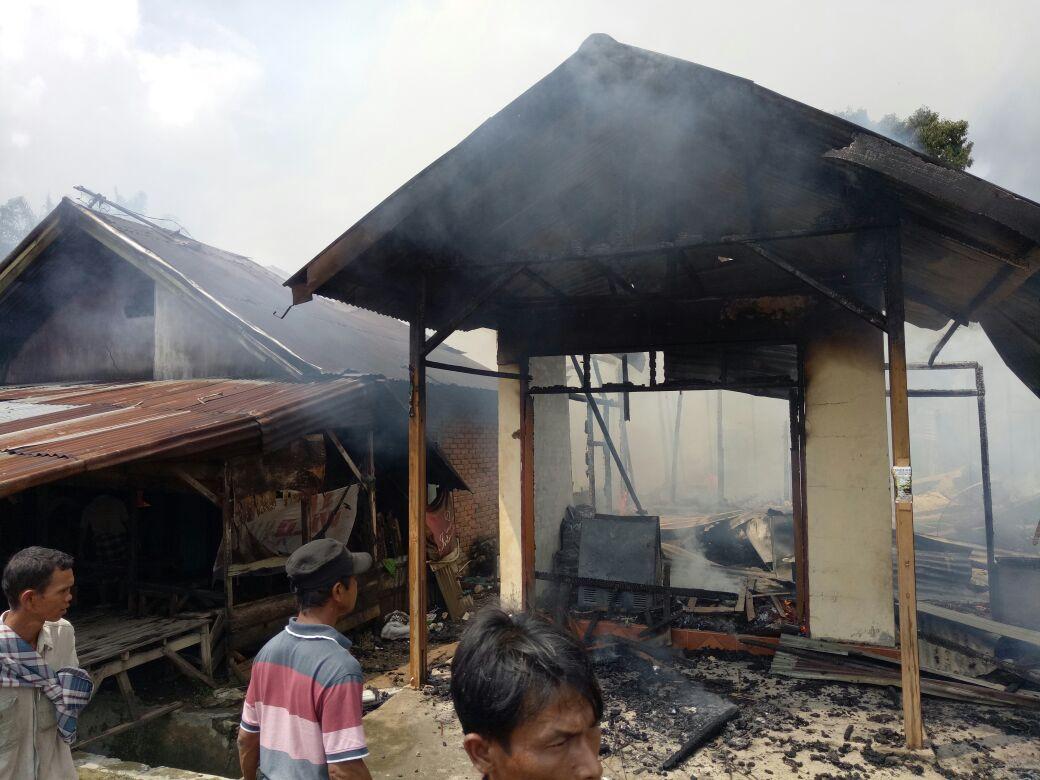 Warga menyaksikan rumah yang terbakar