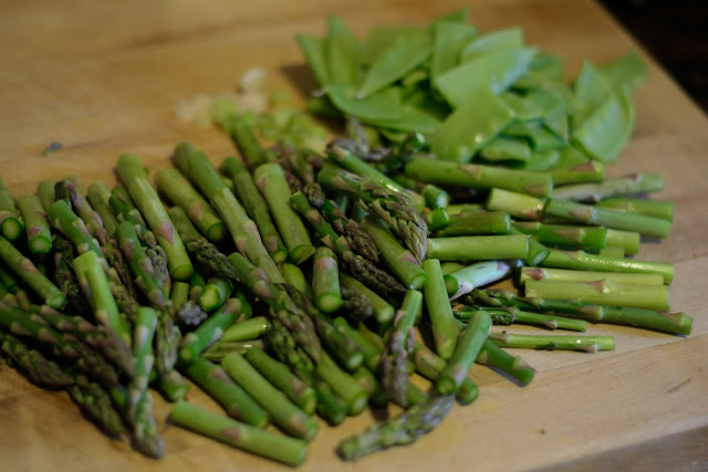 Chopped asparagus, snow peas, green onions, and garlic on a cutting board.