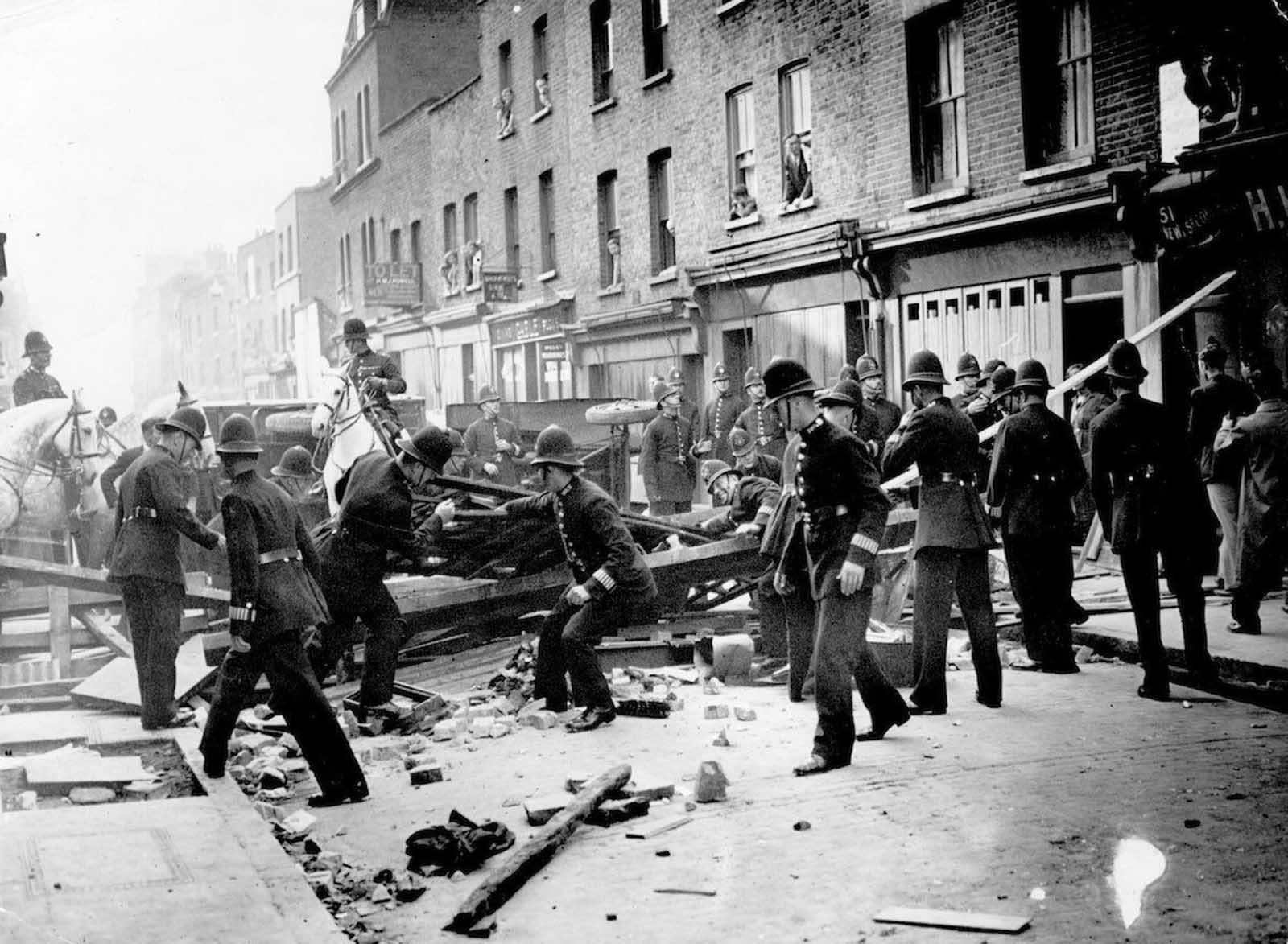 British policemen dismantle a barrier near Mark Lane, London, to make way for a march by supporters of the leader of the British Union of Fascists Oswald Mosley. The barricade was constructed by members of the Communist Party. 1936.