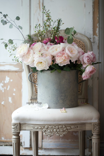 Garden roses in antique zinc bucket on french chair
