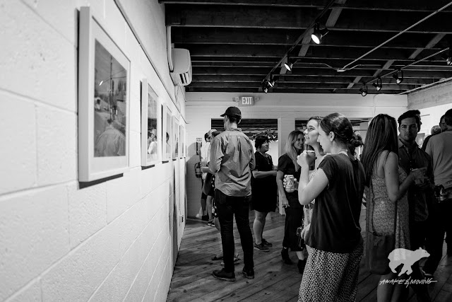 Patrons mingle and view the photographic works of Jason Lee.