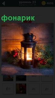 На полке в темном помещении стоит горящий фонарик с хвойными ветками рядом