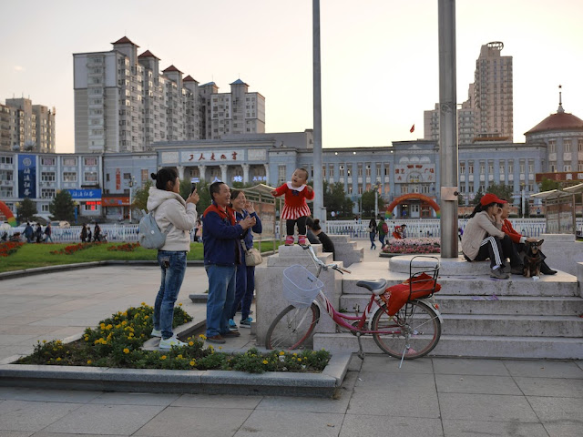 Adults clapping for a toddler singing and dancing at Culture Square in Mudanjiang, China
