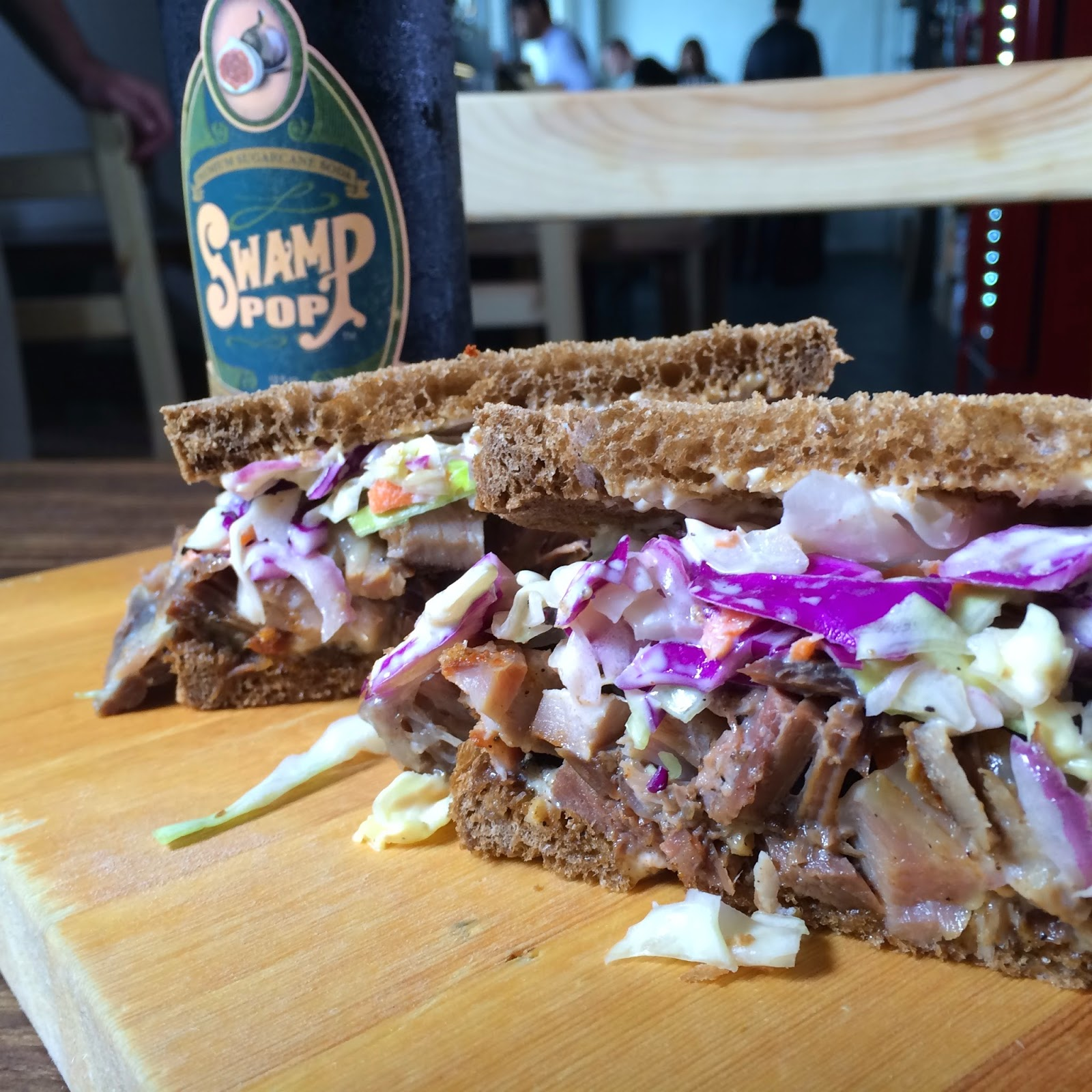 The Chop Block Melt on Rye: Pork Cheek Pastrami, Corned Beef & Smoked Beef Tongue, Slaw, Swiss and Celery Salt Mayo. Pictured with a Swamp Pop Noble Cane Cola.