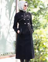 Güneş gözlüklü ve tesettürlü bir bayanın üzerindeki siyah uzun manto