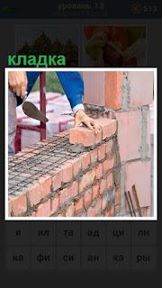 рабочий делает кладку кирпича, укладывая на сетку с цементом