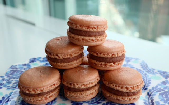 Mini pyramid of chocolate macarons sitting on a blue Anthropologie plate on a white table.