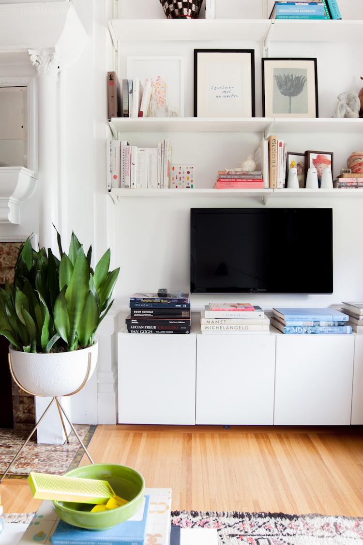 Tv colgada pared y estanterías