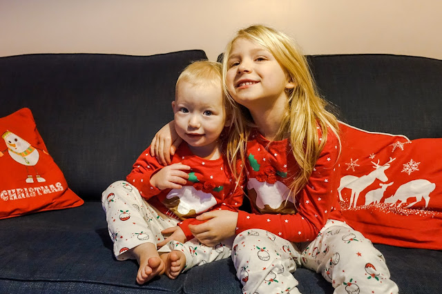 Two sisters on a sofa in Christmas PJs from tesco