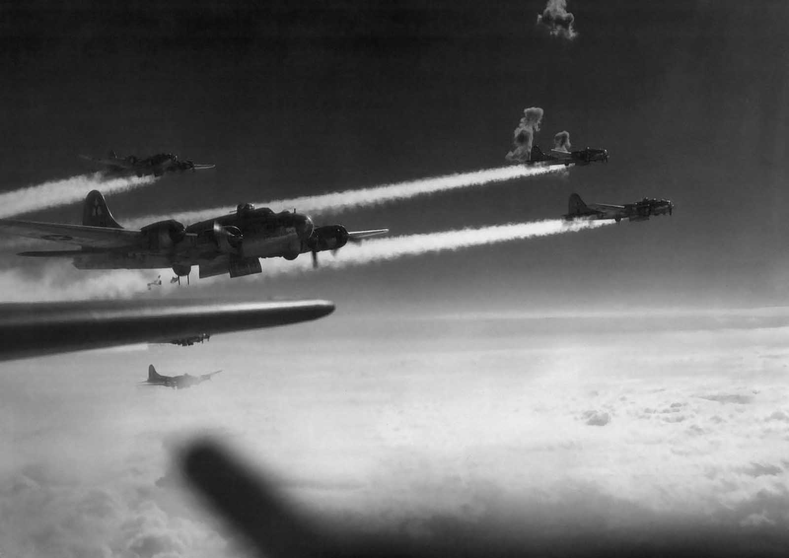 Flak bursts through the vapor trails from B-17 flying fortresses of the 15th air force during the attack on the rail yards at Graz, Austria, on March 3, 1945.