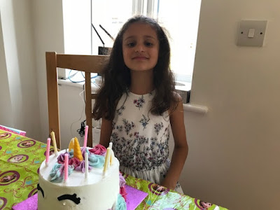 Child with a unicorn birthday cake