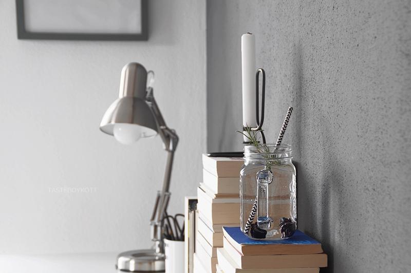 Henkelglas am Arbeitsplatz | Schreibtisch im skandinavisch-minimalistischen Stil herbstlich dekorieren mit umgedrehten Bücherstapeln, Kerzen, Leuchte, Objektiv und Designletters Becher in schwarz, weiß, grau, natur, braun | Tasteboykott