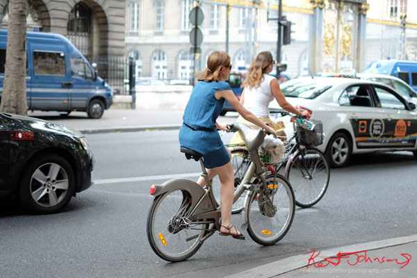 two women cycling in Paris traffic wearing summer outfits. Paris photos by Kent Johnson for Street Fashion Sydney.