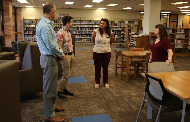 Two men and two women stand in the middle of a library talking