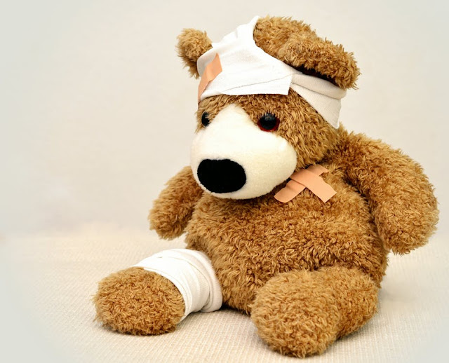 Brown Teddy Bear Wearing Bandages and Band-Aids