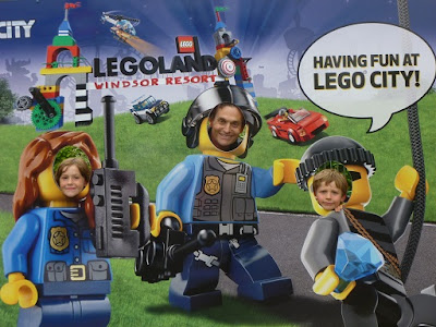 Picture of my husband and children, grinning through holes in a Legoland City poster on our trip to Legoland on a budget