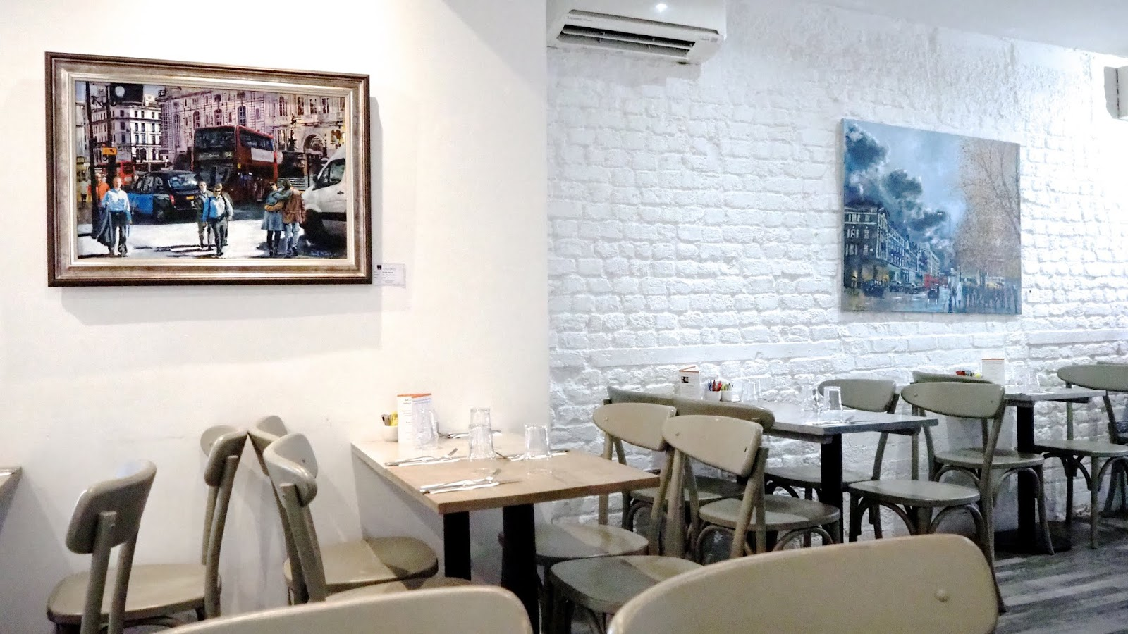 tables & chairs and paintings on the wall at Chelsea Creperie