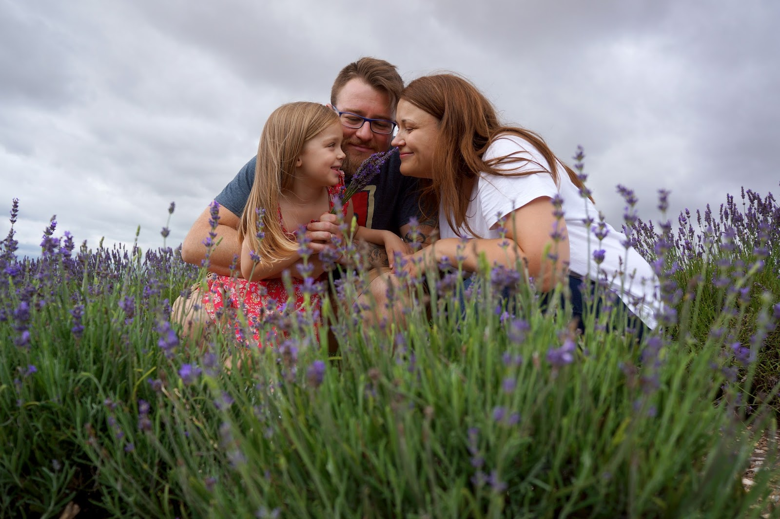 mum dad and daughter smiling family portrait at lavender fields