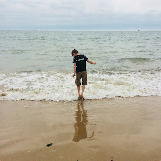 Kids with autism can find some things difficult.  An autistic boy tries to walk in the water at a beach.