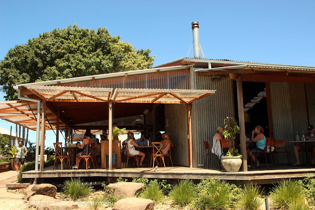 People having lunch on the verandah of a restaurant in a shed.