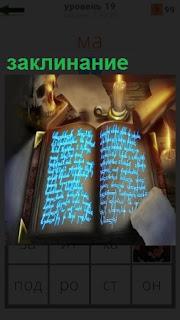 В развернутом виде лежит книга с заклинанием и стоит горящая свеча