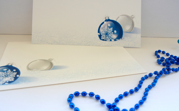 Upclose photo of Cobalt Christmas Postcard and Envelope with a strand of blue beads from Paper Direct