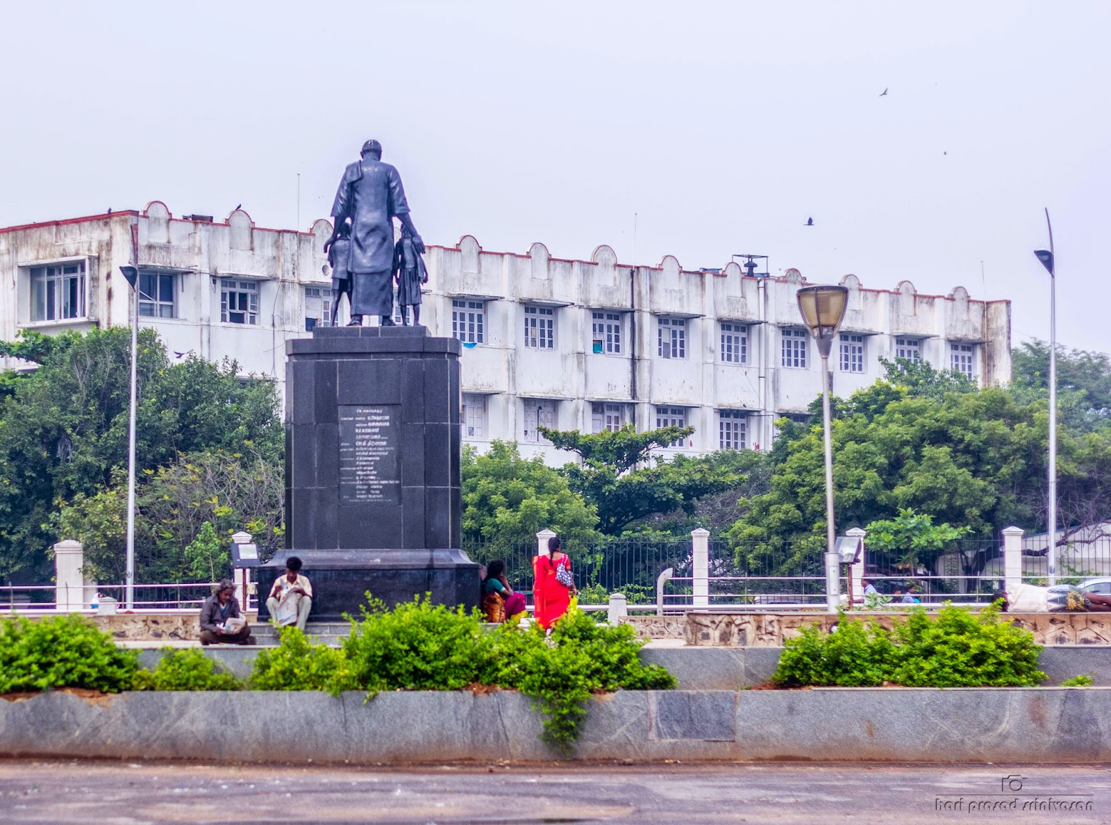 Photo of Kamarajar statue located in Chennai beach. Photo taken from behind the statue on which Kamarajar holds two kids one on each side. Photo taken on a cloudy day.