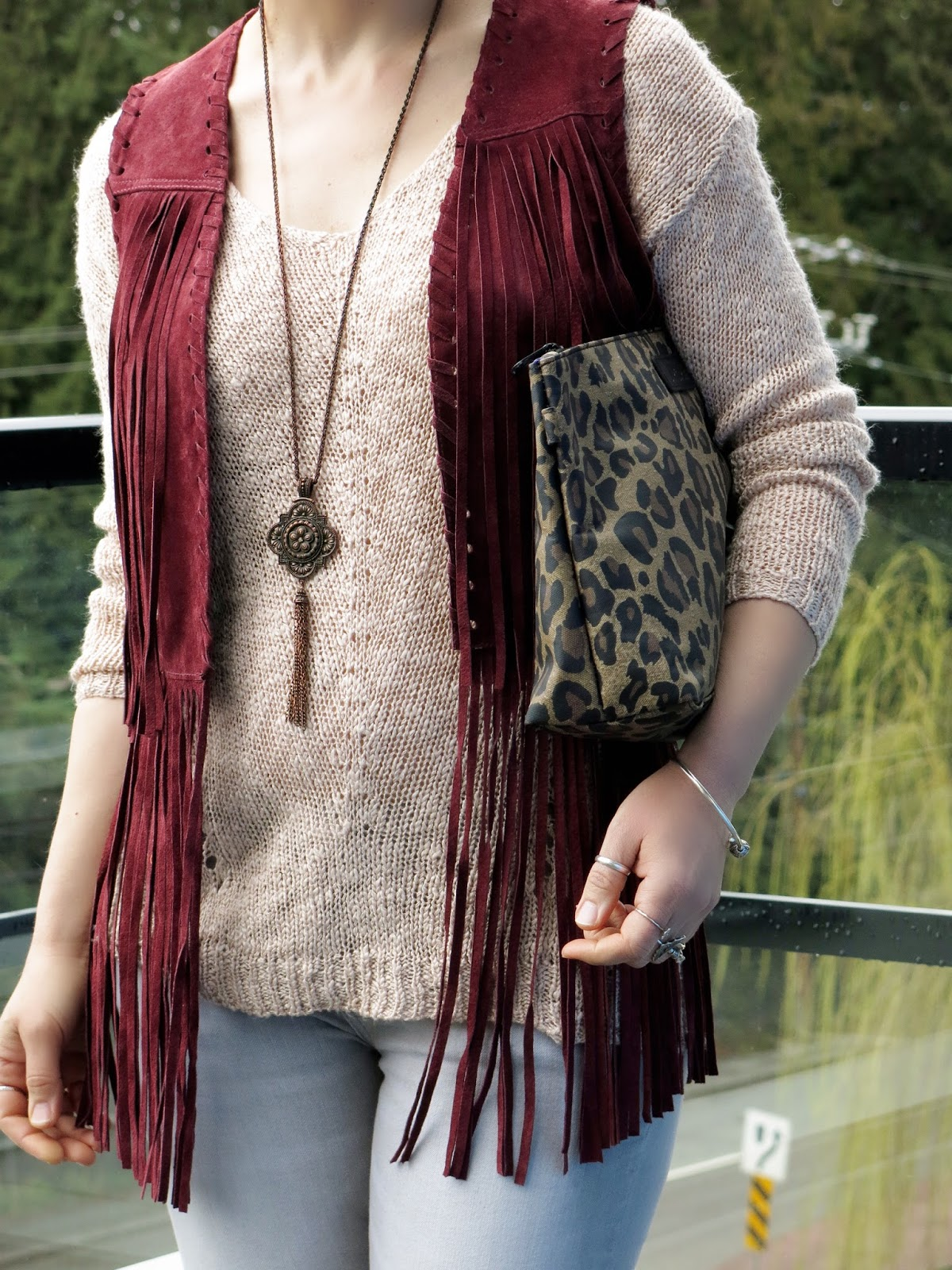 v-neck sweater, fringy maroon suede vest, and leopard clutch