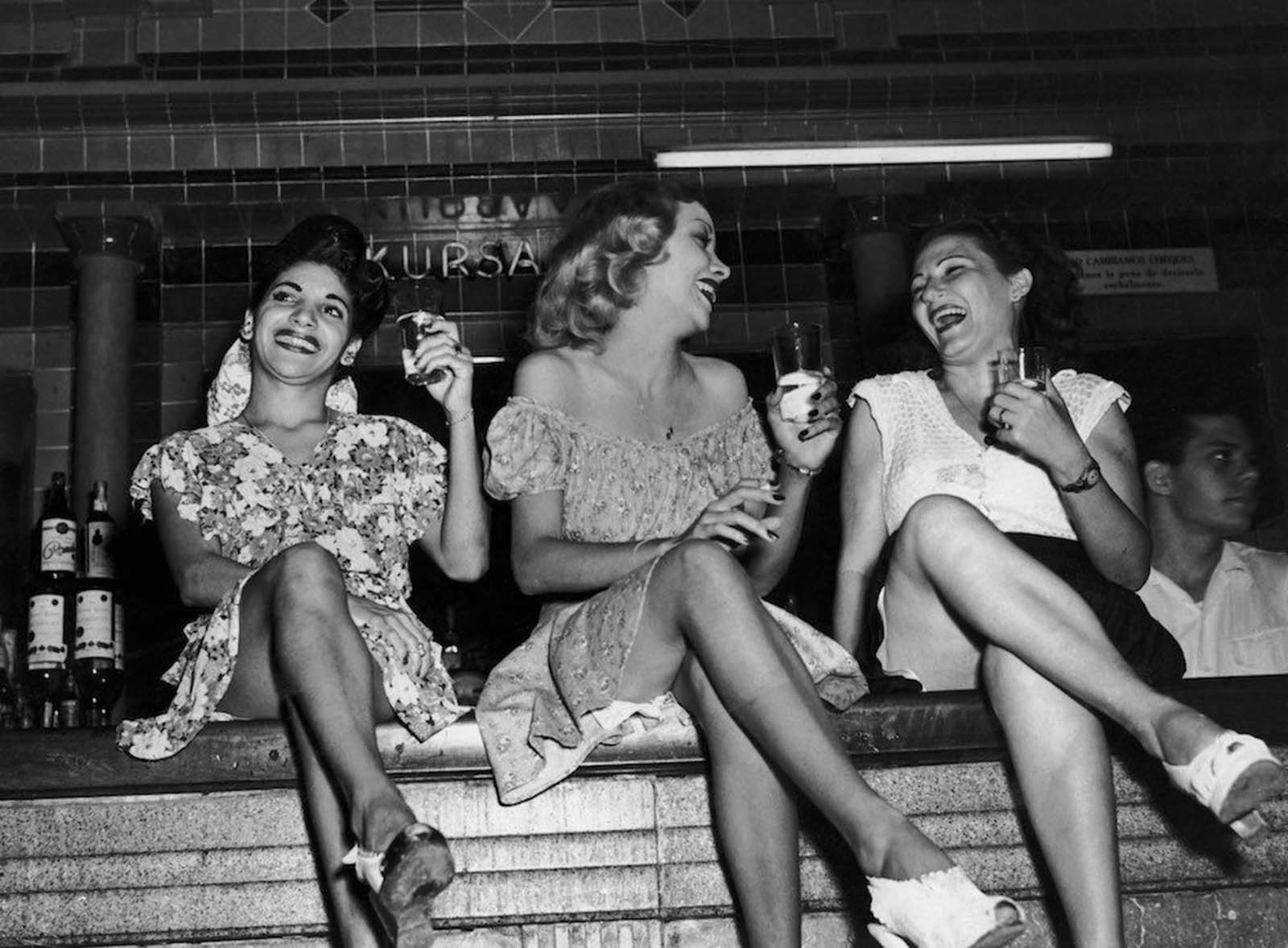 Three women perched on the bar at the Cabaret Kursal nightclub in Havana. 1950.