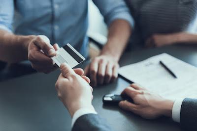 Entrega de tarjeta de crédito en la oficina de alquiler de coches