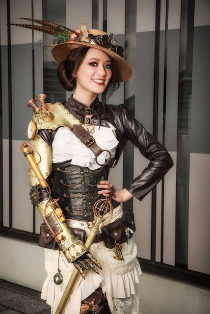 Steamgirl in steampunk clothing with a mechanical arm. Hat, goggles, leather bolero jacket, blouse, skirt, garter, stockings, ankle booties. Women's steampunk fashion.