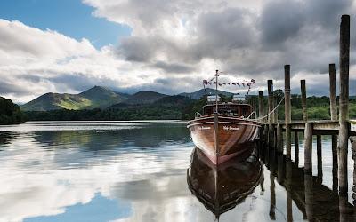 Barco en un lago con montañas y nubes de fondo